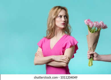 I am sorry. Offended girl is looking bouquet of tulips in male hand with hesitation. She is standing with crossed arms. Isolated and copy space