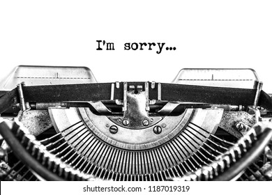 Sorry text typed on retro typewriter, black ink on old paper, close-up