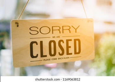 Sorry we are closed sign hang on door at coffee shop.