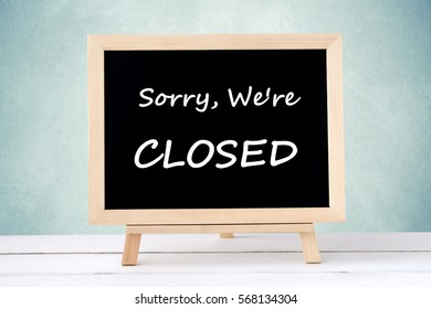 Sorry, we're close on blackboard over green wall background, business hours sign