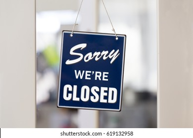 """ Sorry we're closed "" sign in blue and white, on shop glass door with white panels."