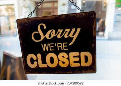 Sorry... WE'RE CLOSED sign in old window with peeling paint