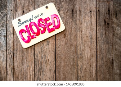 """A 'Sorry We're Closed"""" sign with yellow background and red and black English texts attached to wooden door."""