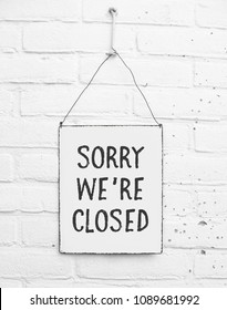 Sorry we're closed - White square metal plate on white brick background - mock up