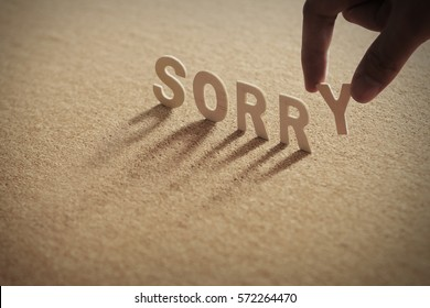 SORRY wood word on compressed or corkboard with human's finger at Y letter.