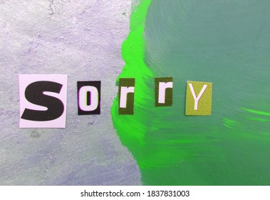 Sorry word from cut out block letters on abstract background