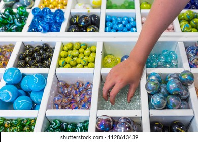 Sorted marbles in various colors in a white wooden sorting box. A child's hand is touching the marbles.