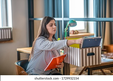 Sorting files. Young woman in a striped jacket sitting on the chair and sorting the files