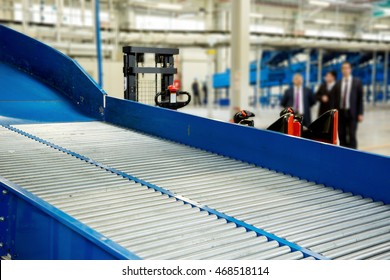 Sorting line with roller conveyor system for transporting crates in large modern warehouse with forklifts