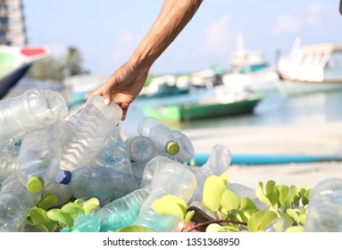 Sorting plastic waste bottles from a pile of plastic bottle at beac