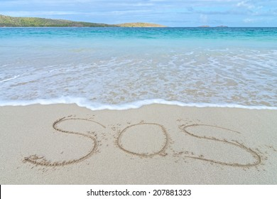 SOS distress sign written in sand of tropical island beach above water