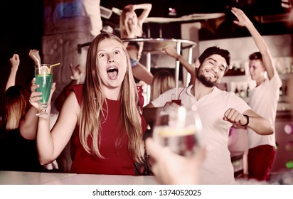Sositive female joying and dancing on party in the club with the cocktail