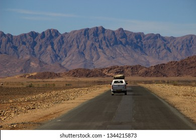 Sossusvlei, Namibia - April 28, 2015: Cars with tourists travel among the stunning landscapes of the Namib Desert, surrounded by mountains