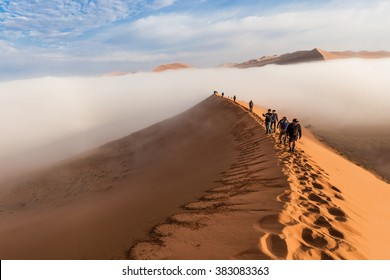 SOSSUSVLEI, NAMIBIA - CIRCA AUGUST 2015 - Tourists climb up the Dune 45 through the early morning fog in Sossusvlei, Namibia.