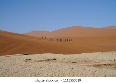 SOSSUSVLEI, NAMIBIA - MAY 15; Sossusvlei dunes at Dead Vlei and white  salt pan cracked into patterns and group of tourists tramping through dunes May 15 2018 Sossusvlei Namibia