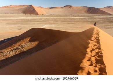 SOSSUSVLEI, NAMIBIA - NOVEMBER 2 2013: Tourists climb Dune No.45 in a year that was declared as a drought year by the government in Namibia, Africa