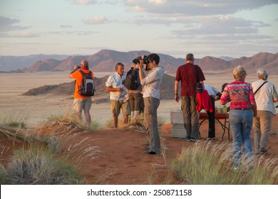 SOSSUSVLEI PARK, NAMIBIA -  MAY 6, 2014: a group of tourists during a safari stop in the namibian landscape. They are enjoying the sunset, photographing the panorama and having a snack