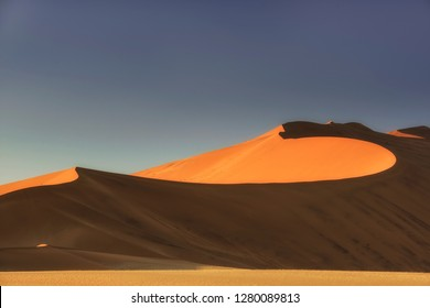 Sossusvlei salt pan with high red sand dunes in Namib desert, Namibia, Africa.