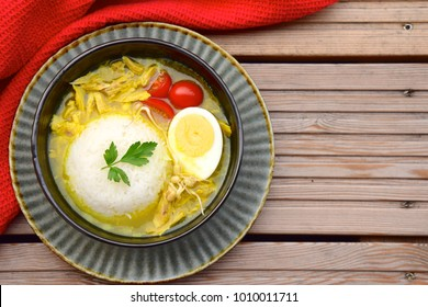 Soto Ayam, yellow spicy chicken soup with egg, tomato, bean sprouts and rice