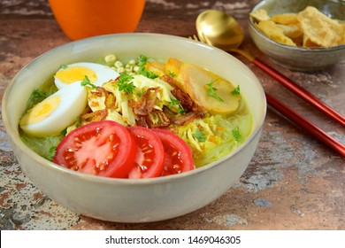 Soto Ayam, yellow turmeric chicken soup with vermicelli noodles, shredded chicken, boiled egg, fried potato, sprouts, tomato, parsley and fried shallots, served with Emping. Popular Indonesian food