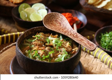 Soto Batok. Javanese beef clear soup with bean sprouts and rice; served in a traditional bowl made of coconut shell, locally known as 'batok'. Accompanied with side dishes and condiments.