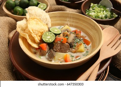 Soto Betawi. Traditional beef and offal soup from Betawi, Jakarta. The soup has been preplated in a bowl; ready to be served. It is surrounded by some of the condiments.