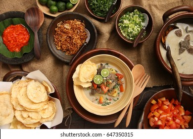 Soto Betawi. Traditional beef and offal soup from Betawi, Jakarta. The soup has been preplated in a bowl; ready to be served. It is surrounded by the soup and condiments.