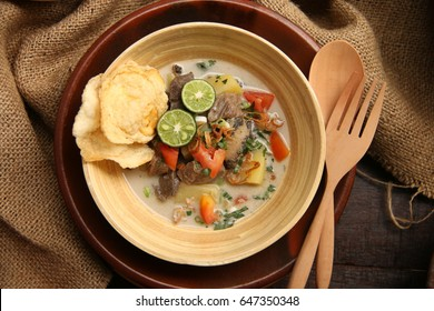 Soto Betawi. Traditional beef and offal soup from Betawi, Jakarta. Served in a bamboo bowl on an earthenware plate, with wooden spoon and fork. Placed on a wooden table; decorated with sackcloth.