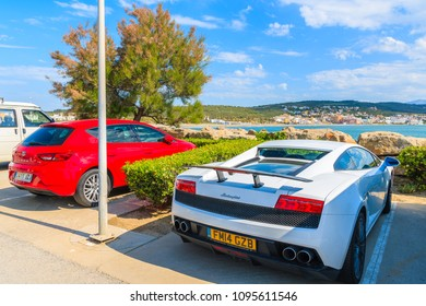 SOTOGRANDE MARINA, SPAIN - MAY 8, 2018: White Lamborghini sport car parking on street in front of a beach in Sotogrande yacht port. Costa del Sol is famous tourist destination on Iberian peninsula.