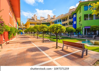 SOTOGRANDE MARINA, SPAIN - MAY 8, 2018: Courtyard with beautiful colorful houses and apartments in Sotogrande yacht port, Costa del Sol, Spain is popular holiday destination in Europe.