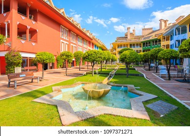 SOTOGRANDE MARINA, SPAIN - MAY 8, 2018: Water fountain and beautiful colorful houses and apartments in Sotogrande yacht port on Costa del Sol. Spain is popular holiday destination in Europe.