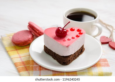 souffle cake in the form of heart  with cup of coffe and macaroons on a wooden table