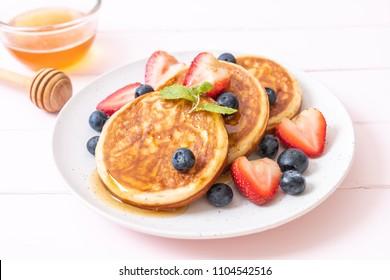 souffle pancake with fresh blueberries, fresh strawberries and honey