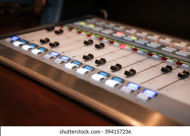 Sound dials and illuminated buttons on an audio mixing board