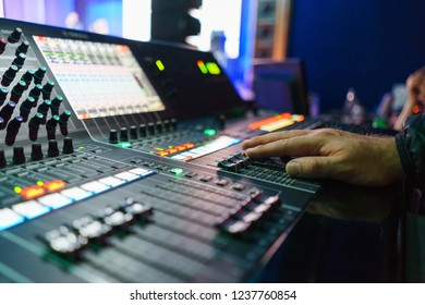 Sound engineer during work, a person manages the equipment during the event. Sound design of a large concert or festival. Modern equipment with a touchscreen and a large LCD screen.