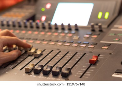 sound engineer hand working on audio mixing console. focus on red fader. recording, broadcasting, editing, post production concept
