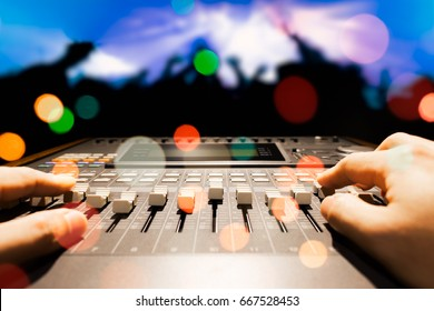 sound engineer hands working on sound mixer in live concert