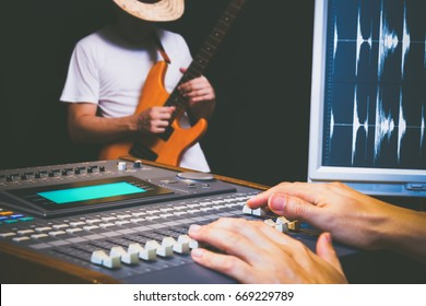 sound engineer hands working on digital sound mixer for electric guitar recording in music studio