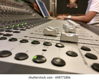Sound engineer mixing in studio with master mixer.