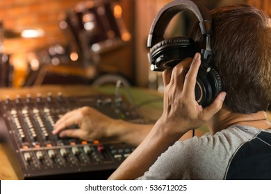 Sound engineer music producer adjusting and balancing audio input to digital mixer in recording studio,bokeh ,blurred background of drum kit.Man holding headphone listening live sound.