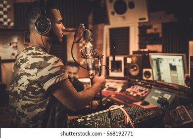 Sound engineer and musician recording song in boutique recording studio.