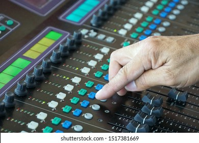 Sound engineer pushing the button on mixer console to adjust sound system.