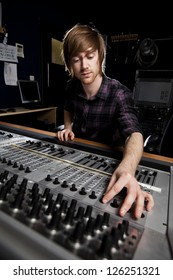 Sound engineer using a studio mixing desk. Selective focus on Sound desk.