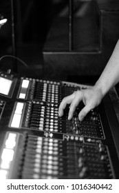 The sound engineer at work behind a mixing console at a concert