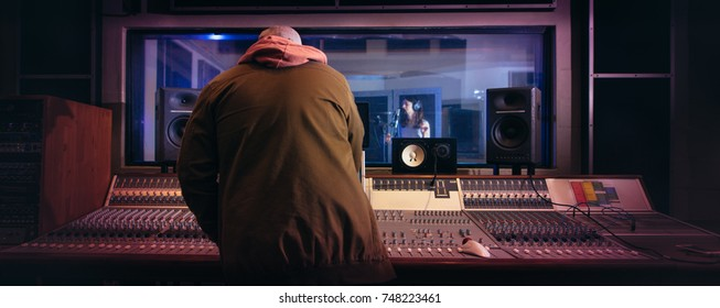 Sound engineer working at audio control panel with singer singing in recording room in background. Musicians producing music in professional recording studio.