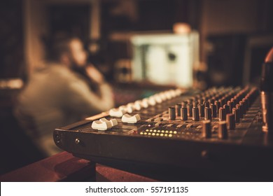 Sound engineer working at mixing panel in the boutique recording studio