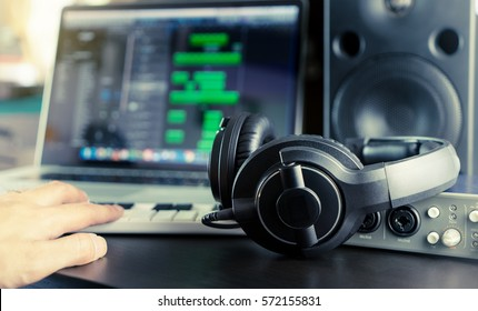 Sound engineer is working on his home music work station mixing Audio sound on a song on his laptop DAW station and headphone.