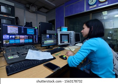 Sound engineer, young woman, working with a mixer control panel at the TV studio. November 11, 2019. Kiev, Ukraine