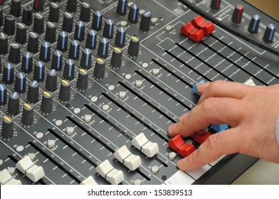 sound engineer's hand moving sliders on audio mixing board