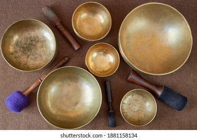 Sound healing music  instruments for meditation, relaxation, yoga, massage, sound healing - tibetan singing bowls with sticks on the dark background - Shutterstock ID 1881158134